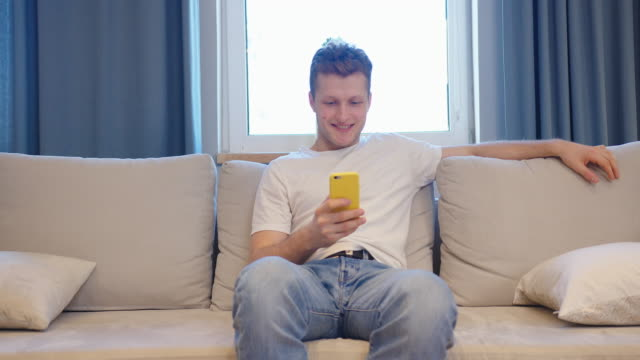 Smiling man in white t-shirt sitting on sofa and using his smartphone