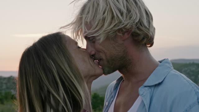 夕日の間にガールフレンドにキスをする笑顔の男 - 対面点の映像素材/bロール