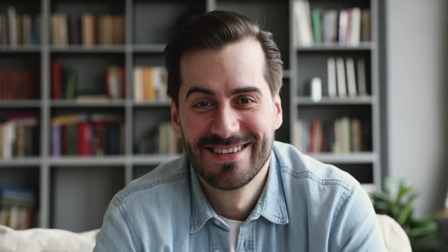 smiling man look at camera talk make videocall at home - machać filmów i materiałów b-roll