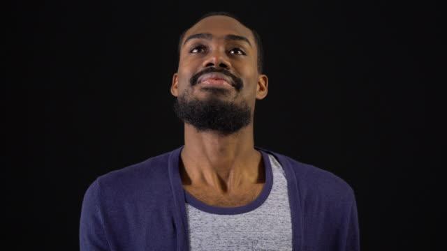 lächelnder mann meditiert auf schwarzem hintergrund - atemübung stock-videos und b-roll-filmmaterial