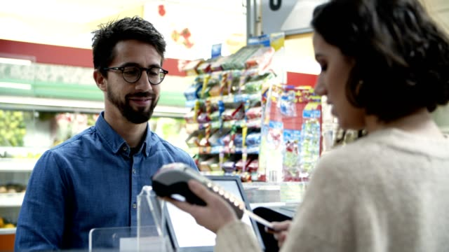 Smiling man paying with credit card in store