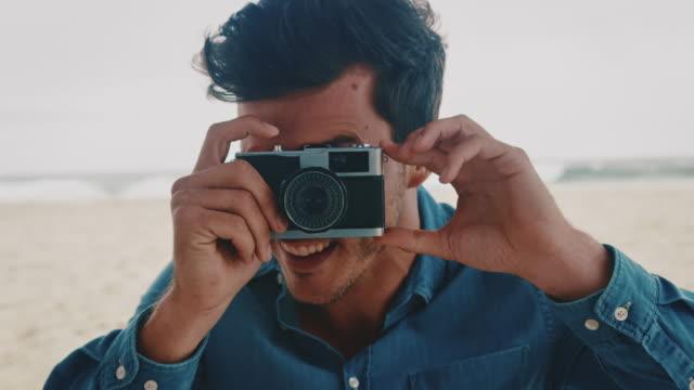 Smiling man photographing through camera at beach