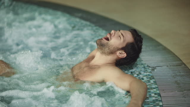 jakuzi spa kapalı rahatlatıcı gülümseyen adam. jakuzi banyosunda dinlenen seksi adam - spa tedavisi stok videoları ve detay görüntü çekimi