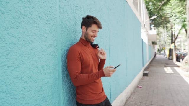 vidéos et rushes de homme de sourire utilisant le téléphone portable. - 30 34 ans