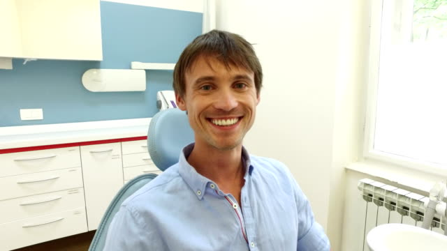 Smiling man with healthy white teeth at dentist video