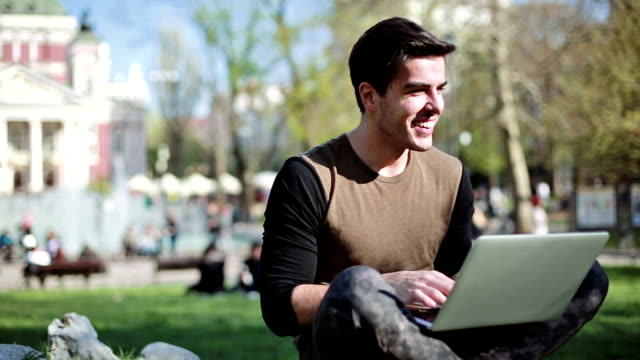 Smiling man with laptop outdoors video