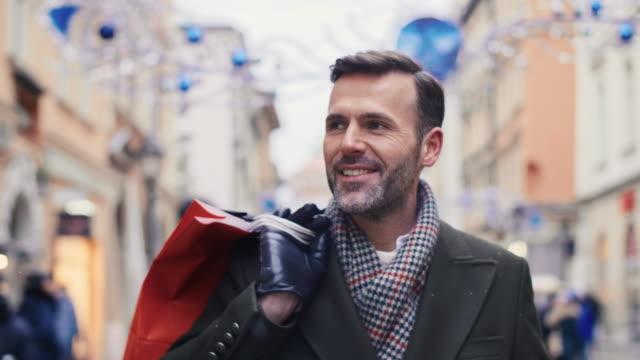 vídeos de stock e filmes b-roll de smiling man with shopping bags walking down the city street - passagem de ano