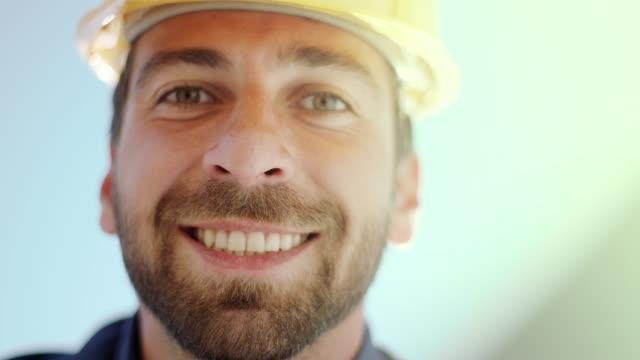 smiling man working on blueprints - imprenditore edile video stock e b–roll
