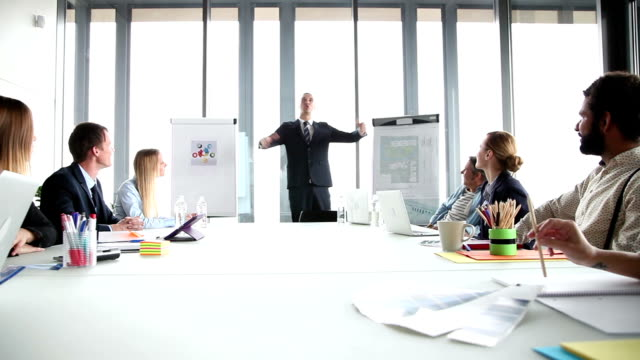 Smiling manager leading a meeting in conference room video
