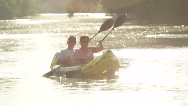 SLOW MOTION: Smiling mature couple canoeing along the glittering river at golden summer sunset video