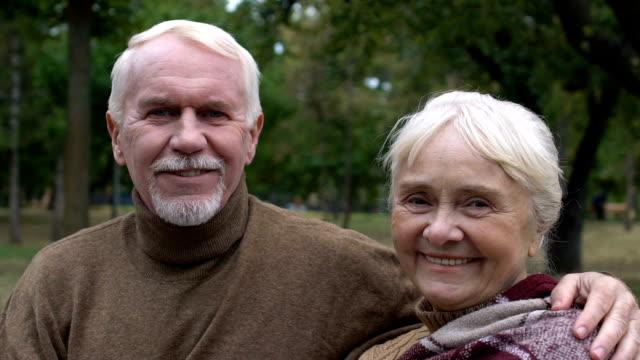 lächelndes reifes paar sitzt auf der bank im park und umarmt, soziale sicherheit - karo stock-videos und b-roll-filmmaterial