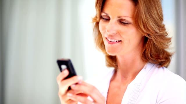 sorridente donna matura leggendo un messaggio di testo - quarantenne video stock e b–roll