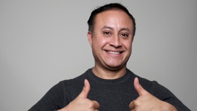 Smiling mature hispanic man posing with his both thumbs up