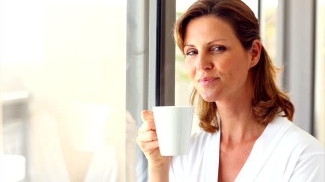 donna matura sorridente con una tazza di caffè - femminilità video stock e b–roll