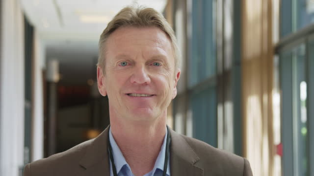 Smiling mature male CEO standing in corridor