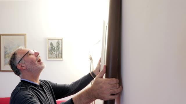 smiling mature man hanging picture  frame on wall in apartment - wisieć filmów i materiałów b-roll