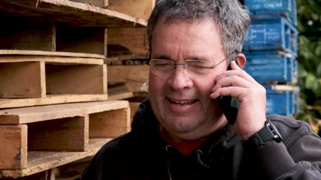 vídeos de stock, filmes e b-roll de homem maduro de sorriso que fala usando seu telefone esperto - brasileiro pardo