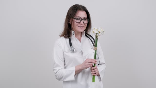 Smiling mature woman doctor nurse with bouquet of flowers, gift, celebration, medical worker day Smiling mature woman doctor nurse with bouquet of flowers, gift, celebration, medical worker day. White background. High quality 4k footage world health day stock videos & royalty-free footage
