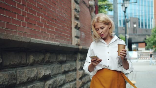 vidéos et rushes de la femme mûre de sourire utilise le smartphone retenant prendre le café marchant à l'extérieur - femmes d'âge mûr
