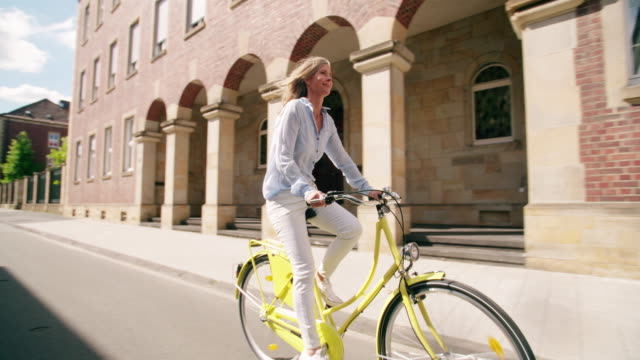 Smiling mature woman riding her bicycle through vintage town video
