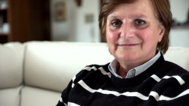 Femme mature souriante assise sur canapé blanc - Vidéo