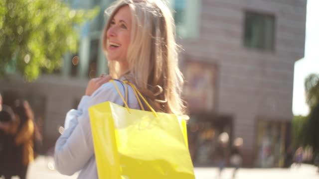vídeos de stock, filmes e b-roll de madura mulher sorridente com sacos de compras, olhando para trás de você - boutique