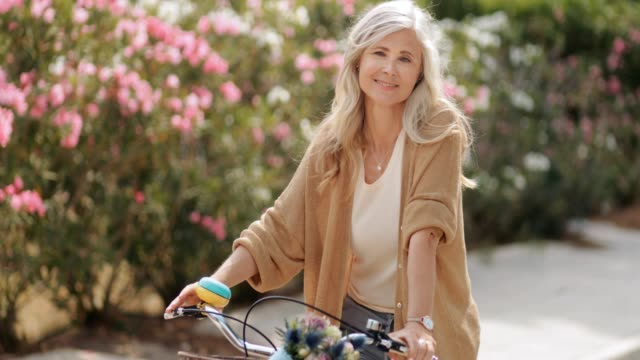 smiling mature woman with vintage bicycle at park in spring - capelli grigi video stock e b–roll
