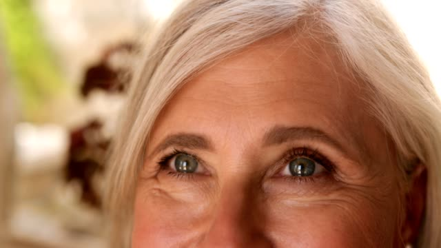 smiling mature woman's face with green eyes and face wrinkles - морщинистый стоковые видео и кадры b-roll