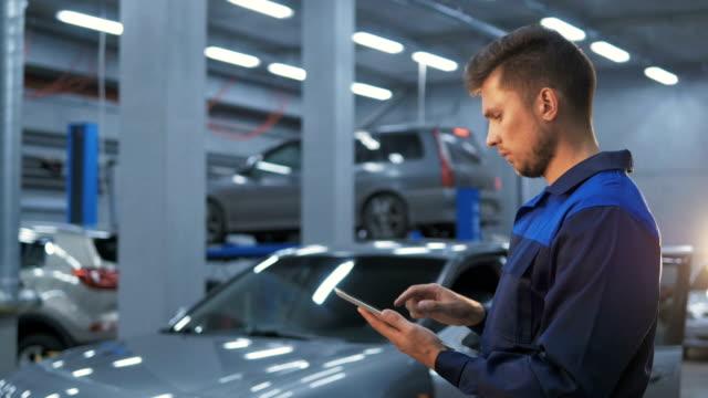 smiling mechanic using a tablet pc at the repair garage service - warsztat filmów i materiałów b-roll