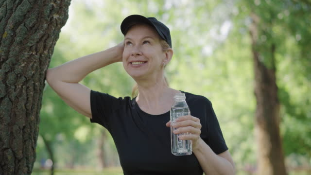 Smiling mid-adult sportswoman leaning against tree in park and drinking water. Portrait of positive Caucasian woman resting after training on fresh air outdoors. Sport, healthy lifestyle. Smiling mid-adult sportswoman leaning against tree in park and drinking water. Portrait of positive Caucasian woman resting after training on fresh air outdoors. Sport, healthy lifestyle. one mid adult woman only stock videos & royalty-free footage
