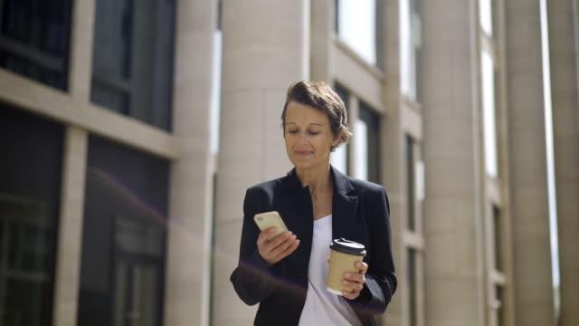 vídeos y material grabado en eventos de stock de sonrisa medio envejecido a mujer con pelo corto caminando por la calle con taza de café para llevar y mensajes en su celular buscando feliz e inspirado de texto - cabello corto