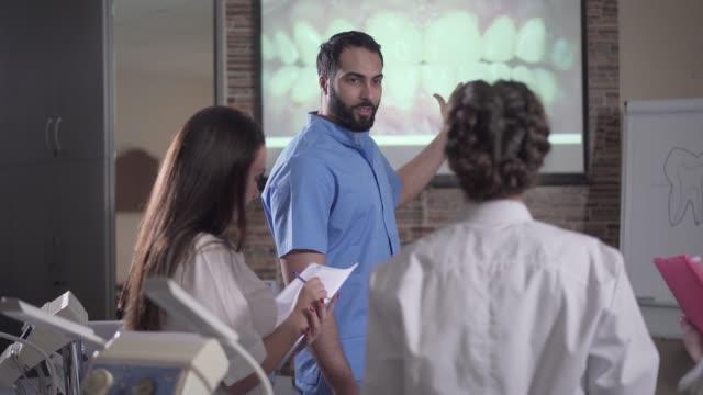 gülümseyen orta doğulu öğretim üyesi ekran önünde diş görselleştirme ile konuşuyor. öğrencilere diş hekimliği dersi veren kendine güvenen genç adam. tıp, öğretim, odontoloji, stomatoloji. - diş sağlığı stok videoları ve detay görüntü çekimi