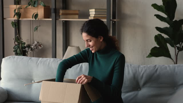 Smiling millennial woman unboxing cardboard parcel at home.