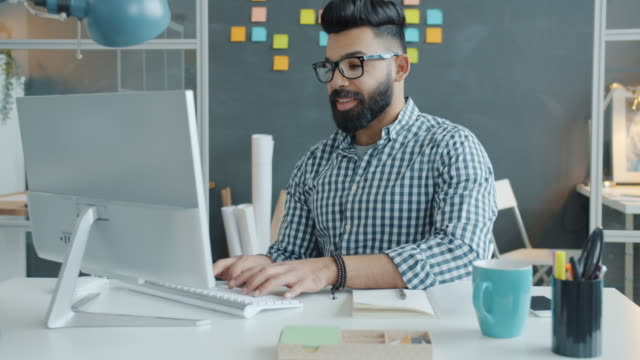 Smiling mixed race man wearing glasses working with computer in workplace video