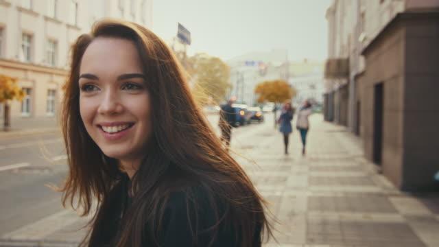 vídeos de stock, filmes e b-roll de modelo sorridente em roupas casuais, andando na cidade de outono - mulheres jovens