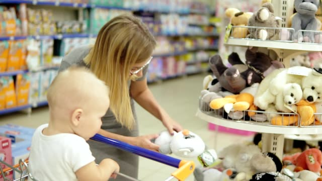 Smiling mother and her child in toy department in the supermarket choosing toys. Cute little baby sitting in a shopping cart and holding a toy. Family shopping