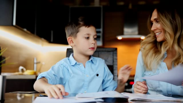 Smiling mother helping his son doing homework, dictates the text to help you write sitting at the table in the kitchen video