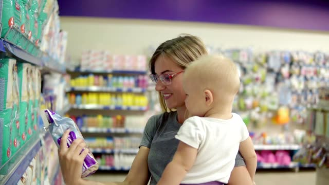 Smiling mother in a section for children in the supermarket holding her child in her arms while choosing diapers on the shelves in the supermarket best products for her child video