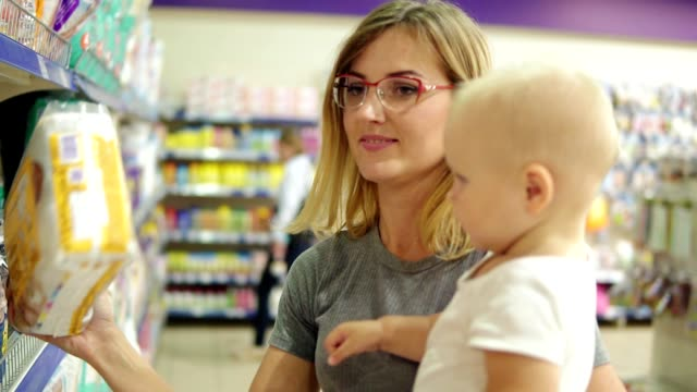 Smiling mother showing her child a package with diapers and asking her opinion in a section for children in the supermarket holding her child in her arms. Family shopping video