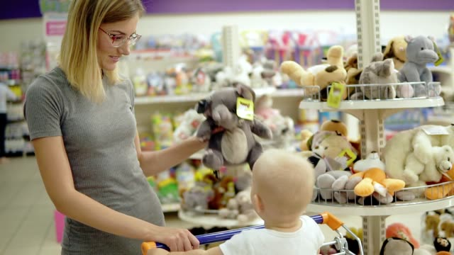 smiling mother showing her child a toy elephant in a toy section for children in the supermarket while her cute little child sitting in a shopping cart. family shopping - giocattolo video stock e b–roll