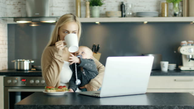 smiling mother sits on the kitchen table before laptop and holds enquisitive child on her knees. mother sips from a cup child reaches out too. - ciuccio video stock e b–roll