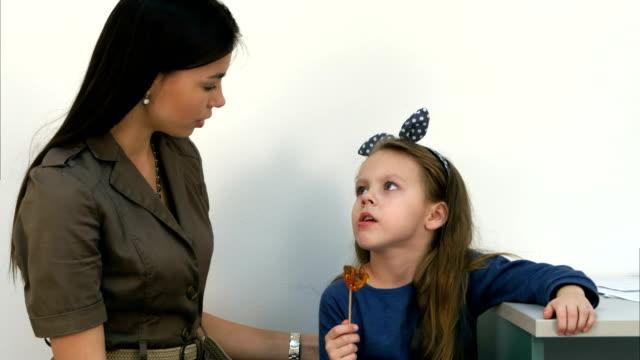 Lachende moeder praten met haar kleine meisje eten een lolly in spreekkamer video