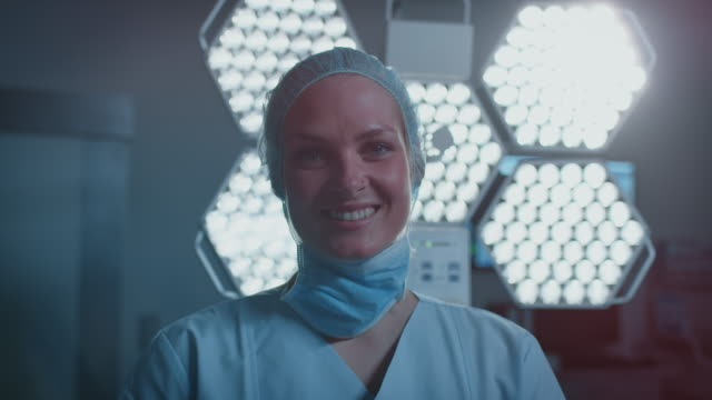 smiling nurse against illuminated surgical light - infermiera personale medico video stock e b–roll