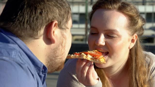 stockvideo's en b-roll-footage met glimlachend zwaarlijvige paar genieten van pizza smaak, voedsel passie, overtollige gewichtsprobleem - dikke pizza close up