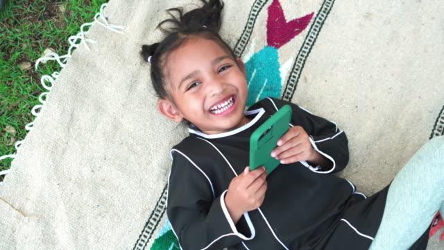 stockvideo's en b-roll-footage met het glimlachen van moslimmeisje dat geluksogenblik met het spelen van een smartphone heeft terwijl het hebben van picknick bij openbaar park in weekend - koran