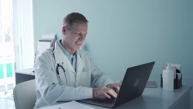 Smiling old doctor using laptop computer sitting at desk in medical office. Smiling old doctor using laptop sitting at desk in medical office. Happy senior physician working consulting patient online, typing, e learning looking at computer. Telemedicine, healthcare technology general view stock videos & royalty-free footage