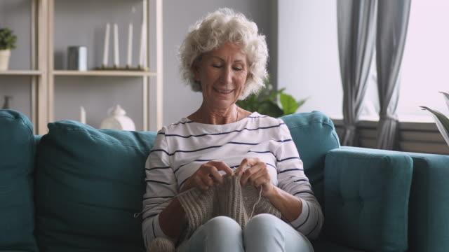 Smiling old grandma knitting scarf enjoying leisure hobby at home