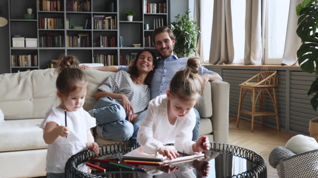 Smiling parents relaxing on couch while little kids drawing.