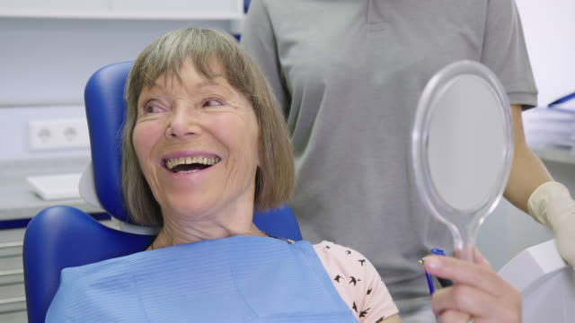 Smiling patient talking while holding hand mirror