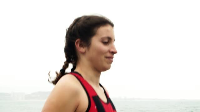 triatleta femminile sorridente che si diverte a fare jogging - triatleta video stock e b–roll
